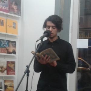 Participante recitando una poesía en el micrófono abiertto